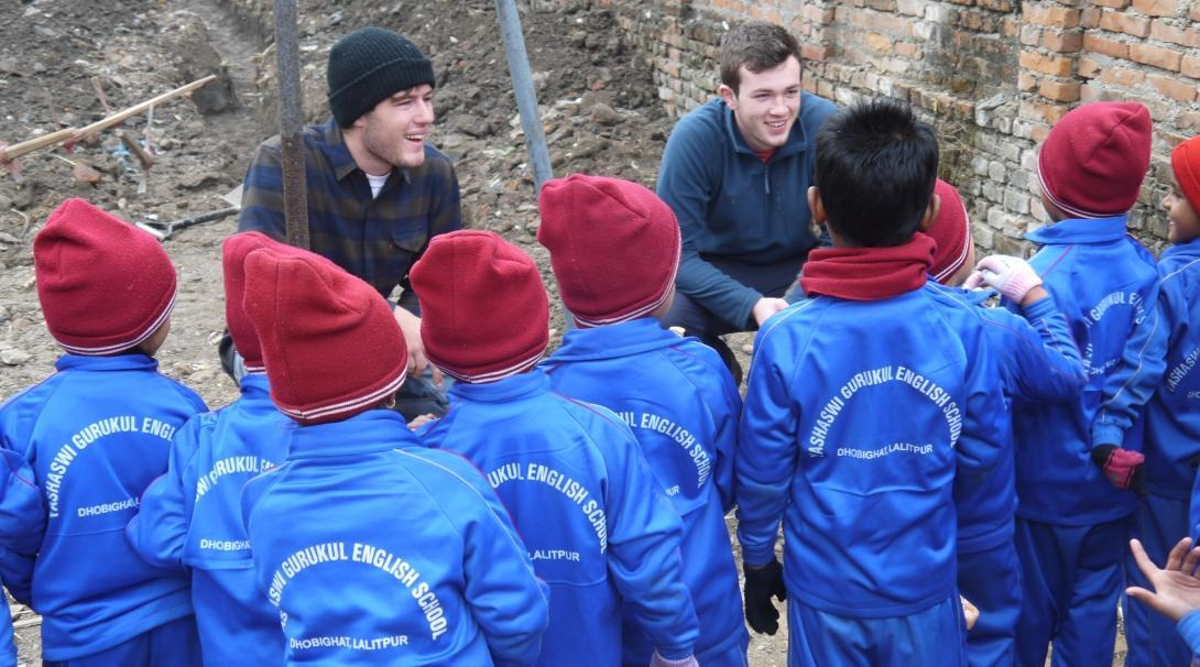 High school student volunteers doing building work in Nepal stop working to talk with young children.